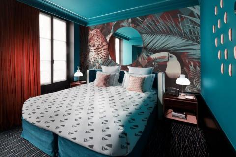 smart-art-leopard-and-toucan-wallpaper-in-a-hotel-room-with-boho-bedding